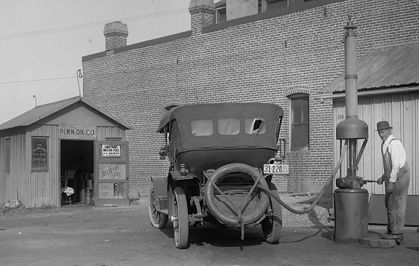 An early gas station attendant fills a n auto gas tank.
